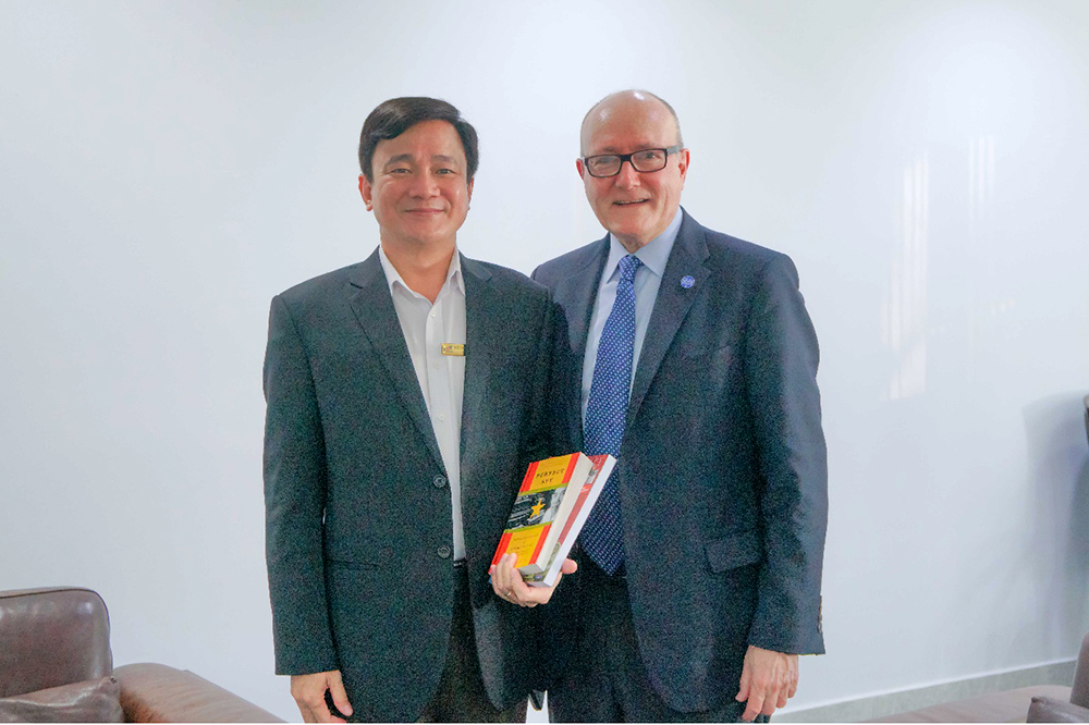 "Prof. Larry S. Berman gives his book titled ""X6- Perfect Spy"" about Pham Xuan An to Prof. Le Vinh Danh, President of TDTU"